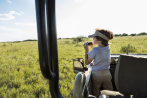 a six year old boy with binoculars in a safari veh K9ZTL86