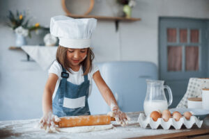 cute kid in white chef uniform preparing food on t 6UCYGGL