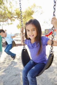 boy and girl playing on swing in park PVBXHG6