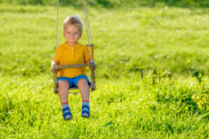 rural scene with toddler boy swinging outdoors P7QE63E
