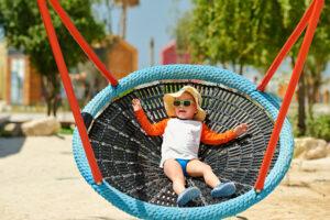 toddler child swinging on beach P4PG8TS