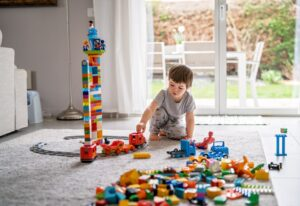 little toddler boy playing with lego train blocks at home at quarantine isolation period during t20 zWPeo4