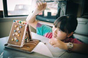 girl making ginger bread house in christmas time t20 WxOBQL