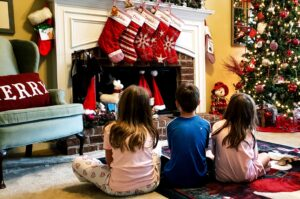 three kids sitting in front of fireplace waiting for santa to climb down their chimney and fill their t20 jR31wr
