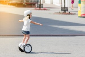 cute kid on the self balancing electric gyro scooter in the park in summer pad rider board t20 XzZQgG