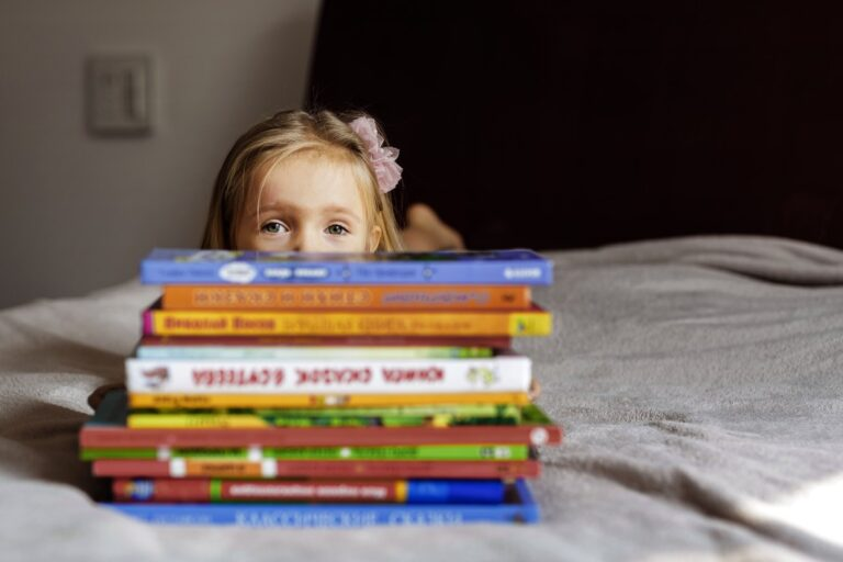 nominated happy little girl lying on the bed and hiding behind a pile of books t20 V7Awvb 2