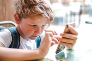 a kid concentrating while using a smartphone t20 doARel