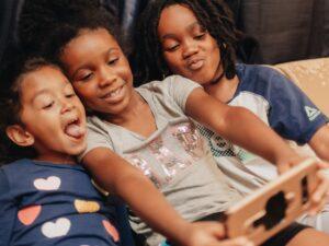 kids using technology technology using technology smartphone selfies fun family african american t20 QKYR4G